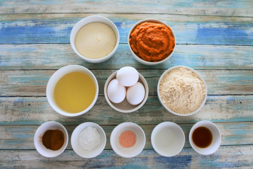 An overhead image of ingredients for a pumpkin spiced loaf including raw cane sugar, pumpkin puree, oil, eggs, whole wheat pastry flour, spices, baking powder, salt, and extracts.