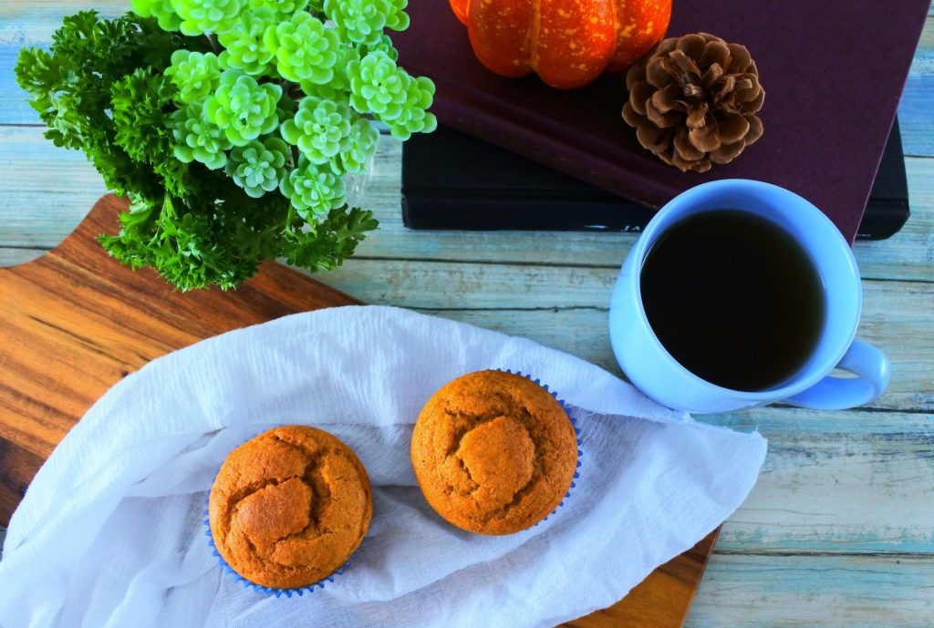 An overhead image of two pumpkin spice muffins on a white cloth on a board with another in the background along with a stack of books with a pumpkin on top, a cup of coffee and some greenery