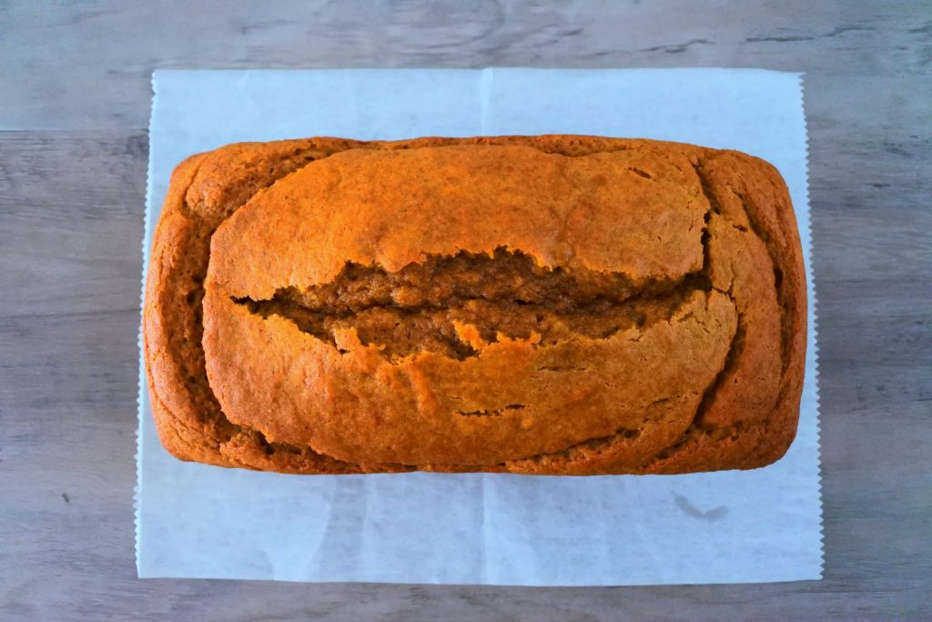 An overhead image of a freshly baked loaf of pumpkin spice bread on a piece of parchment paper