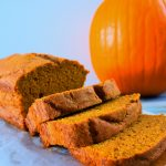 A head on image of sliced pumpkin spice loaf on a board next to a pumpkin