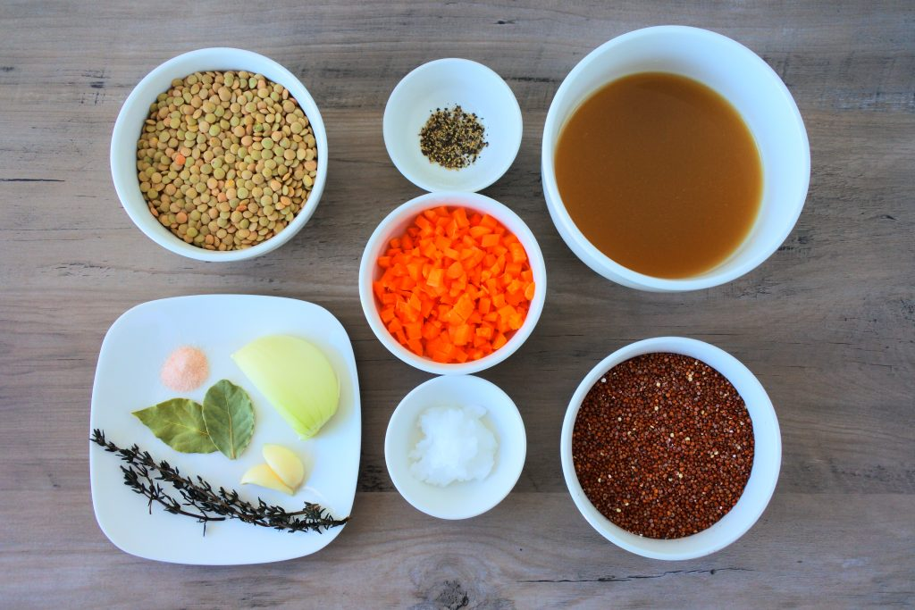 An overhead image of dishes containing the following ingredients for a lentil and quinoa pilaf: lentils, salt, bay leaves, onion, garlic, fine thyme, black pepper, coconut oil, diced carrots, broth and quinoa