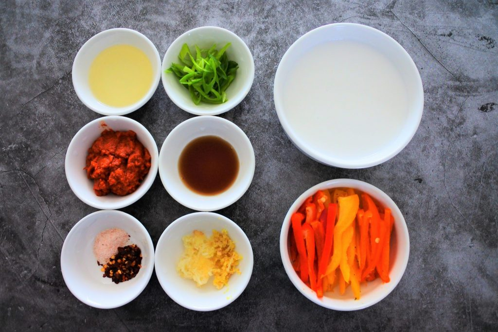 An overhead image of bowls of ingredients for red thai curry including: oil, red curry paste, salt, red pepper flakes, garlic and ginger, fish sauce, green onions, coconut milk and sliced sweet peppers