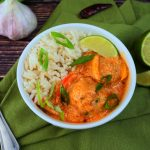 A head on angled image of a bowl of coconut rice with red thai curry and thai chicken meatballs topped with sliced chives and a lime wedge on a green linen napkin with head of garlic, green onions, limes and a red pepper in the background