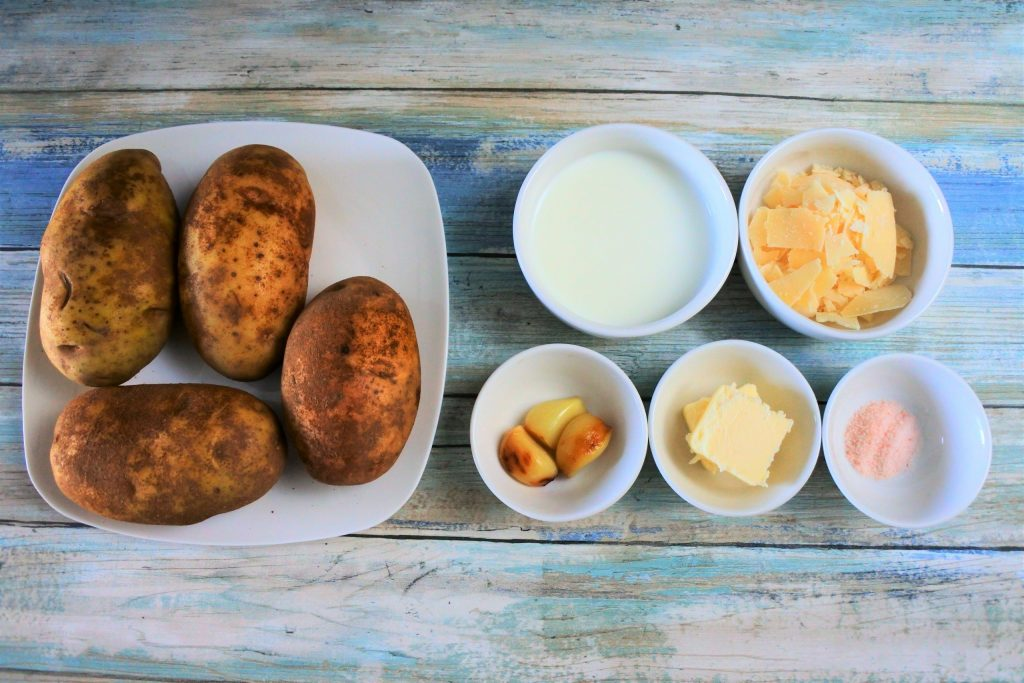 An overhead image of ingredients needed for roasted garlic and parmesan mashed potatoes including whole potatoes, milk, parmesan cheese, cloves of roasted garlic, butter and salt