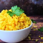 A close up image of a bowl of saffron rice garnished with fresh parsley