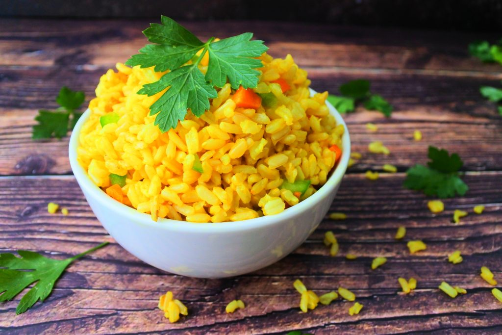 A close up image of a bowl of saffron rice with diced carrots and green bell peppers mixed in and a garnish of fresh parsley