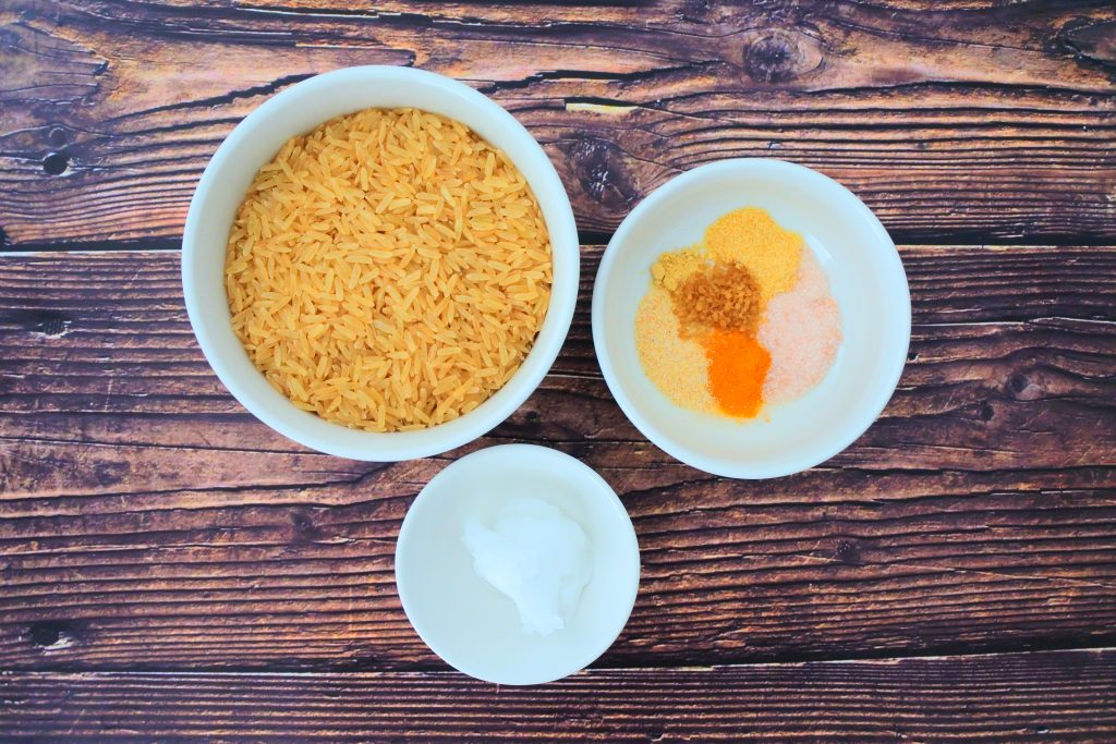 An overhead image of three bowls, one containing brown parboiled rice, one containing coconut oil and the third containing a blend of spices including powdered saffron, onion powder, garlic powder, salt, ginger powder and organic raw sugar