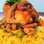 An image of a cornish game hen on a bed of vegetables and some coconut saffron rice