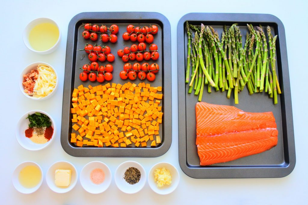An overhead image of trays and dishes of ingredients for a salmon and veggie tray bake including: on the vine cherry tomatoes, cubed butternut squash, asparagus, a salmon fillet, minced garlic, black pepper, salt, butter, lemon juice, herbs and spices, pre-cooked bacon and shredded cheese and oil