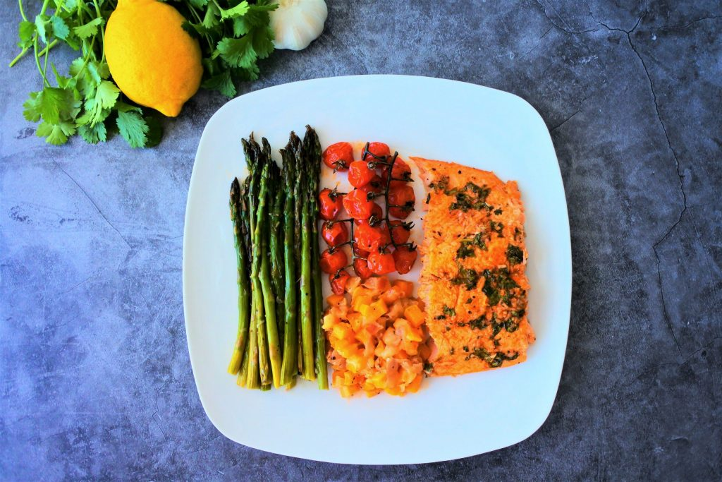 An overhead image of a plate of tray baked salmon with veggies