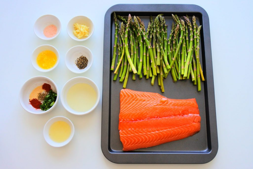 An overhead image of a tray of fresh asparagus and a salmon fillet next to dishes of ingredients needed to season them