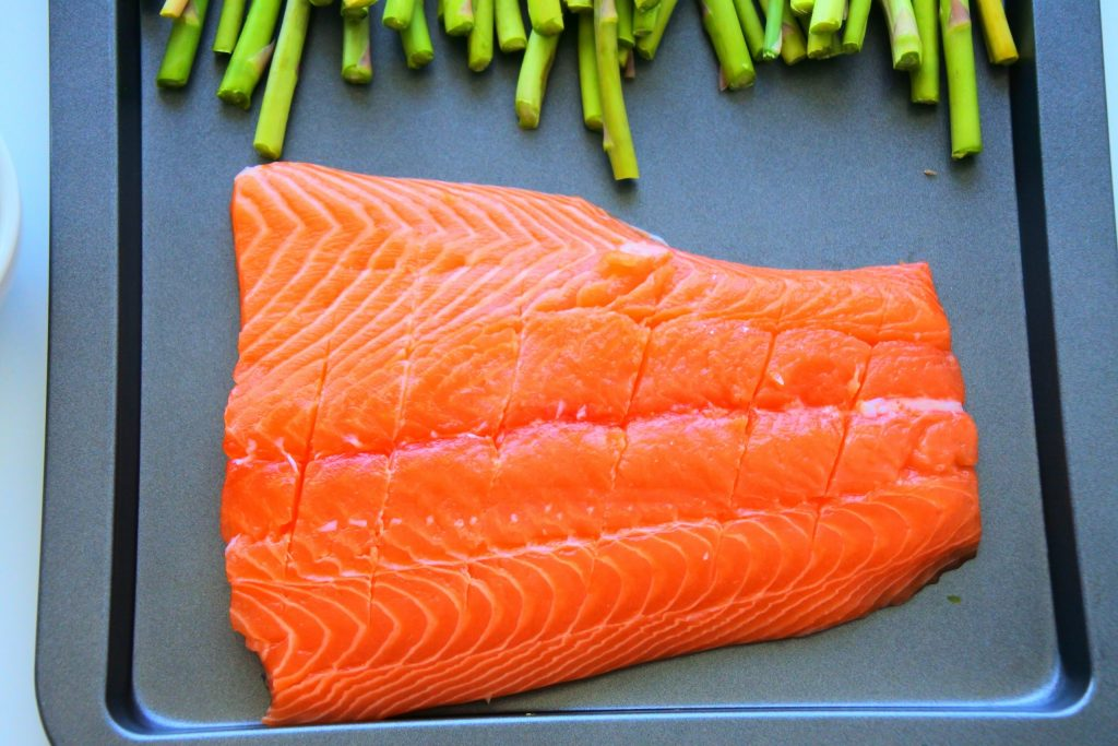 A close up image of a salmon fillet with diagonal score marks sliced into it