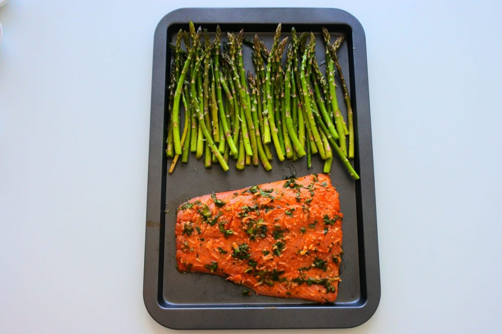 An overhead image of a tray with seasoned asparagus and a seasoned fillet of salmon