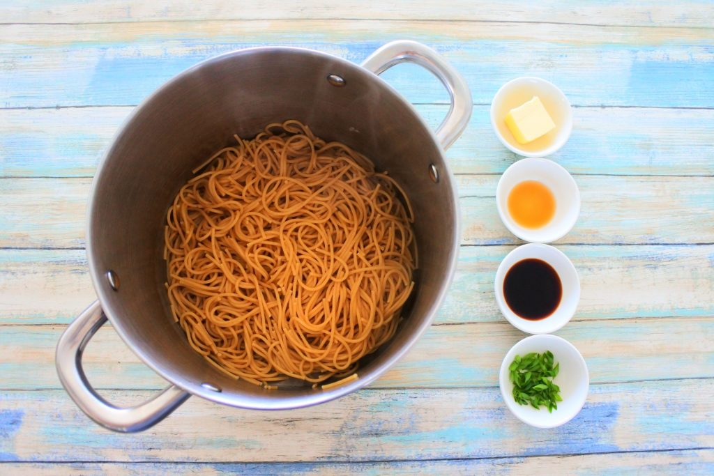 An overhead image of a pot of cooked whole wheat noodles with four smaller dishes next to it containing butter,sesame oil, soy sauce and chopped chives