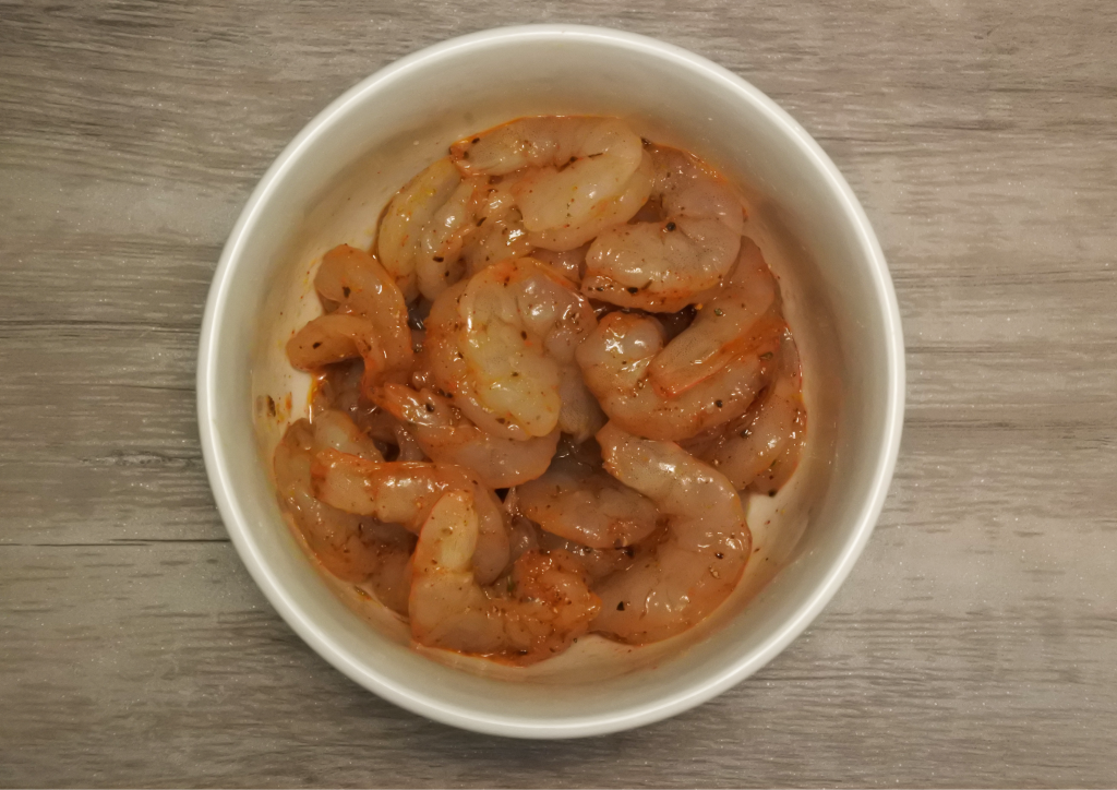 An overhead image of a bowl of uncooked chipotle-seasoned shrimp