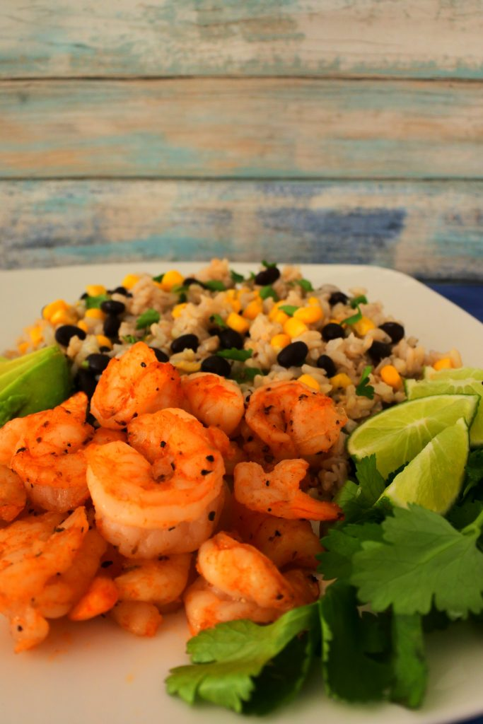 A tilted angle image of a plate of chipotle fried shrimp served with a corn and black bean rice and garnished with fresh parsley and lime wedges