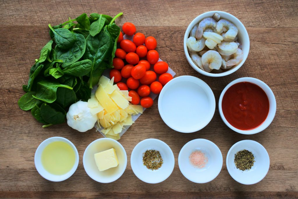 An overhead image of ingredients for Creamy Shrimp and Spinach with Blistered Tomatoes including: spinach, cherry tomatoes, shrimp, garlic, parmesan cheese, coconut milk, tomato sauce, extra light olive oil, butter, dried oregano, salt and ground black pepper