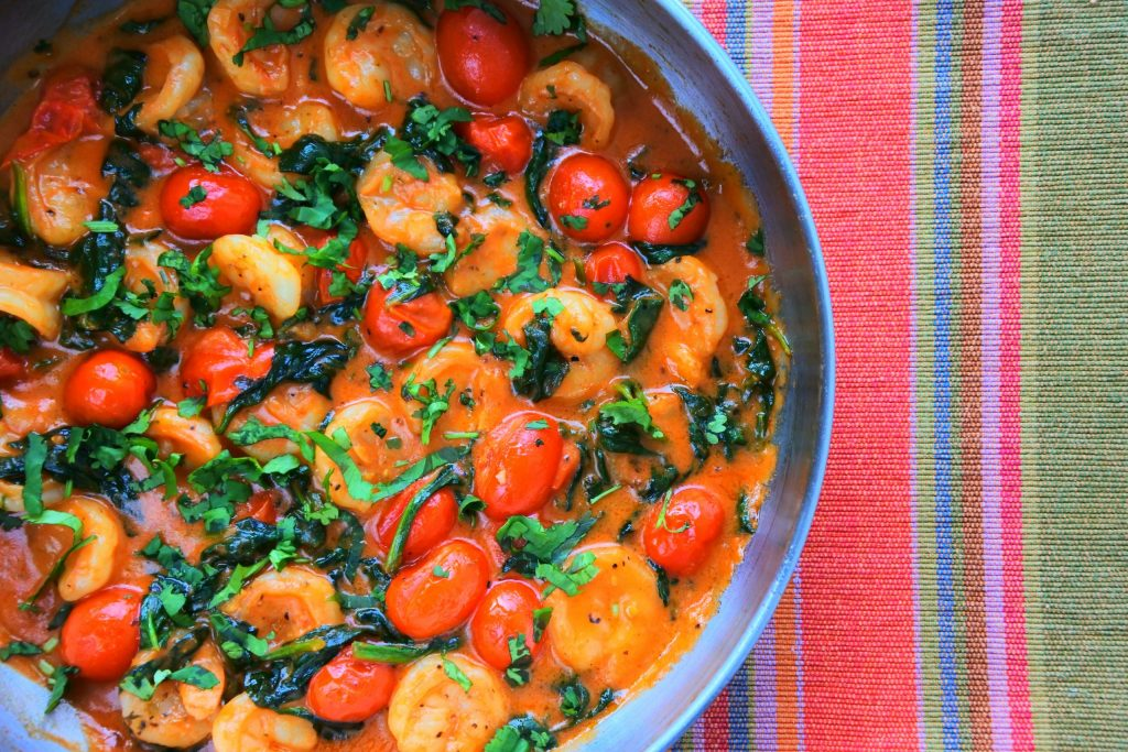 An overhead image of a pan of Creamy Shrimp and Spinach with Blistered Tomatoes