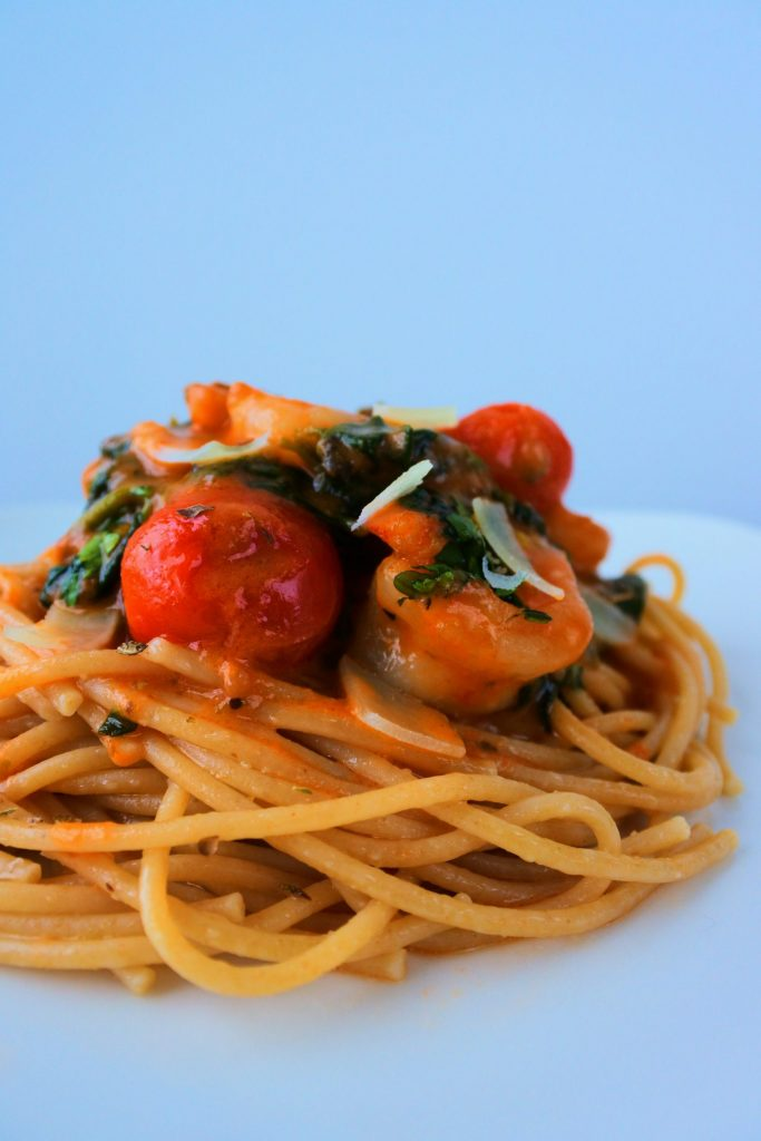 A head on image of Creamy Shrimp and Spinach with Blistered Tomatoes on whole wheat pasta