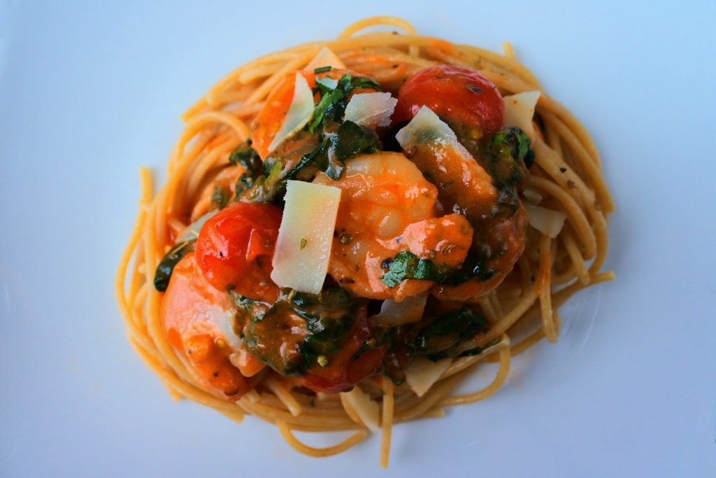 An overhead image of Creamy Shrimp and Spinach with Blistered Tomatoes on whole wheat pasta