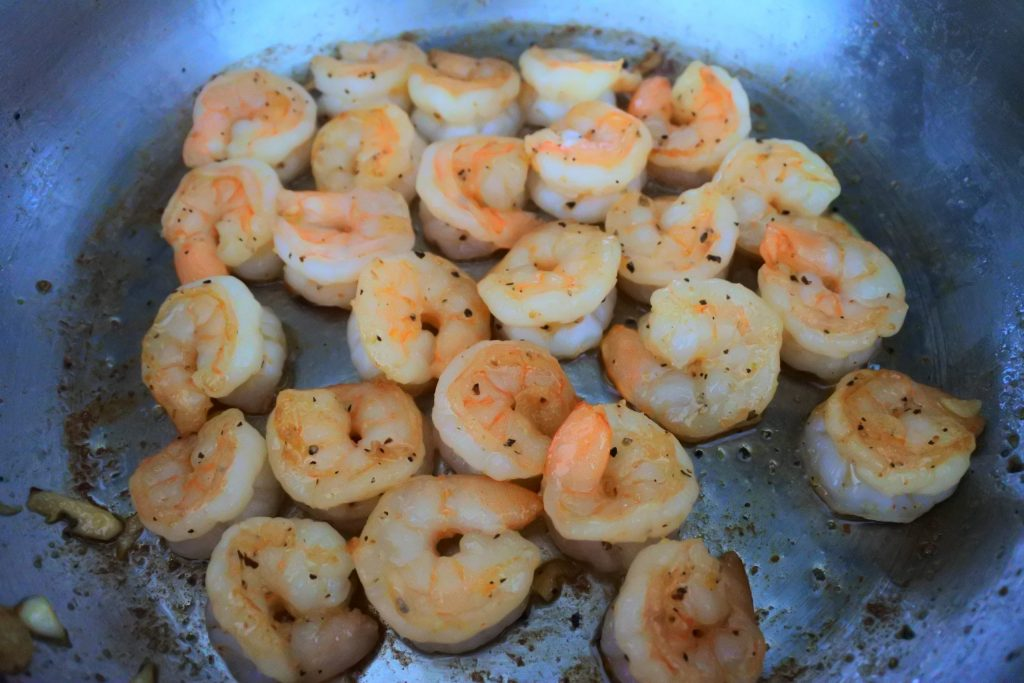 A close up image of seasoned shrimps in a pan