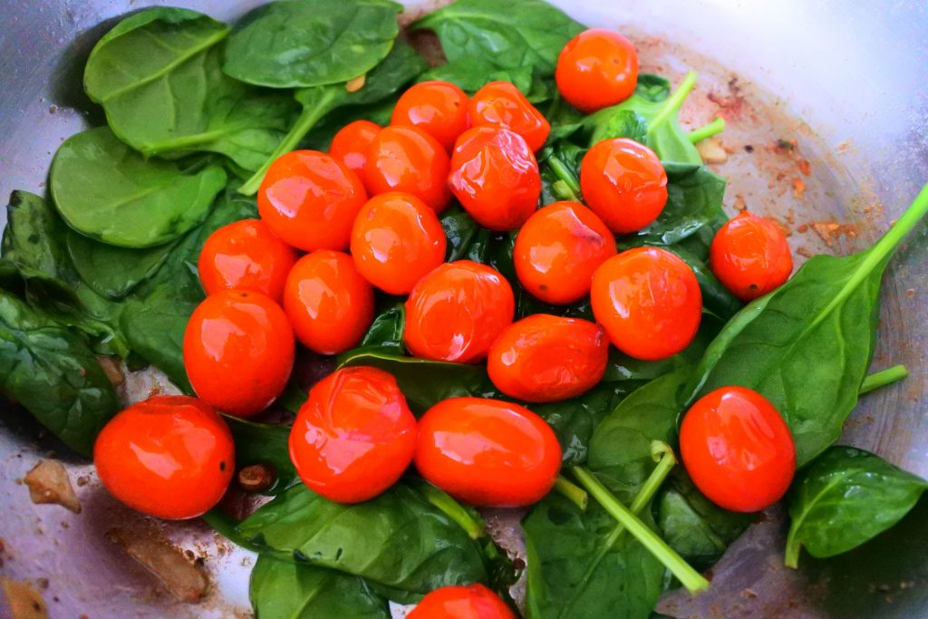 A close up image of spinach and blistered tomatoes in a pan