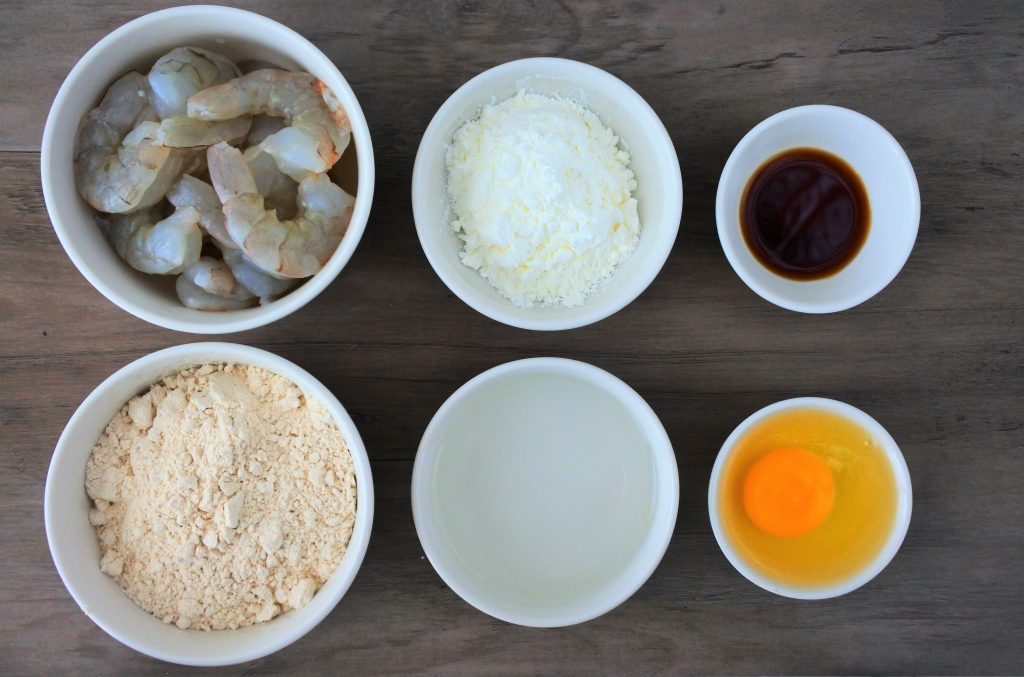An overhead image of six bowls, each containing a single ingredient: shrimp, whole wheat pastry flour, potato starch, ice water, soy sauce, and an egg