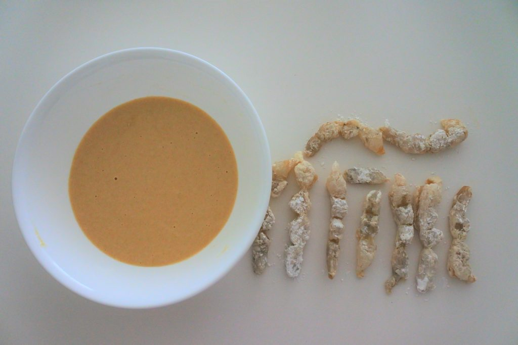 An overhead image of straightened shrimp dusted in potato starch next to a bowl of tempura batter
