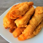 A tilt-towards image of a plate of golden fried shrimp tempura