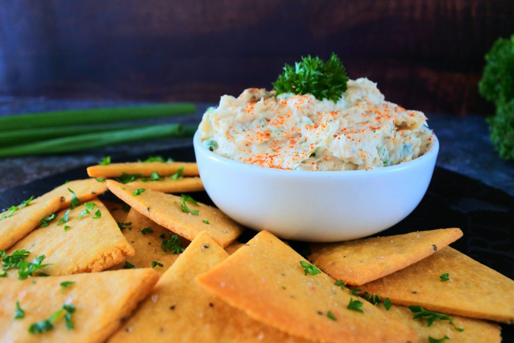A head on image of a dish of smoked trout dip topped with smoked paprika and parsley next to some cheesy chickpea crackers