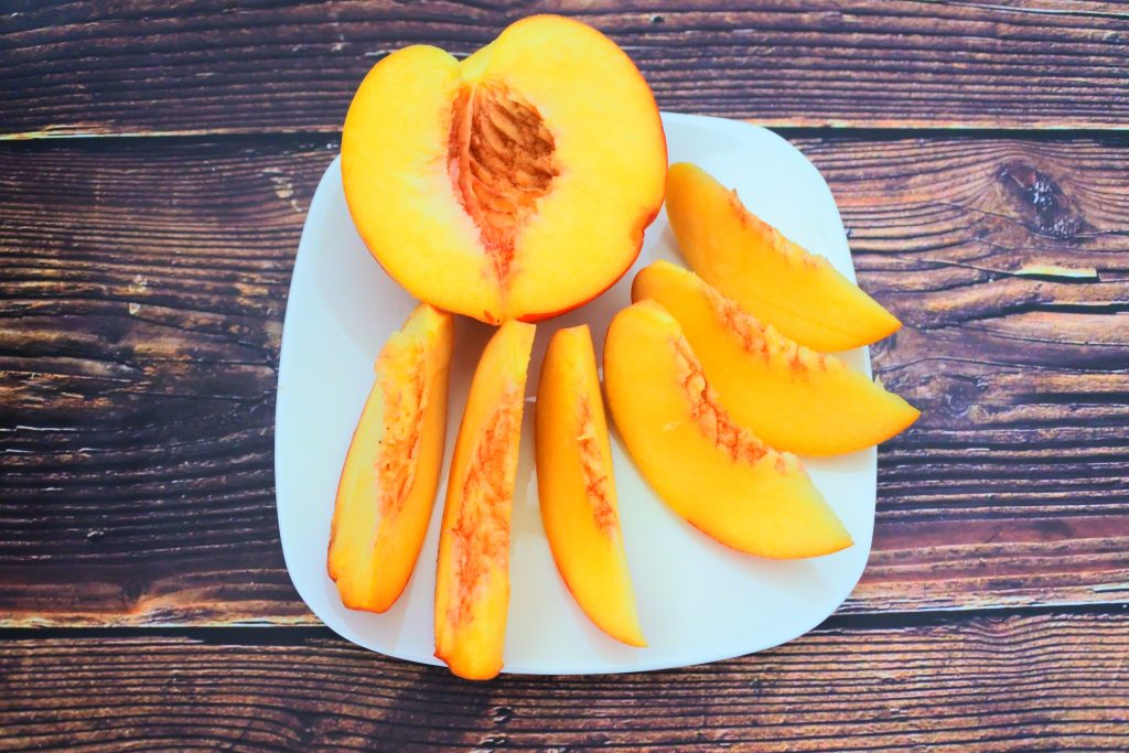 An angled image of a plate containing a ripe half cut fresh peach and several peach slices