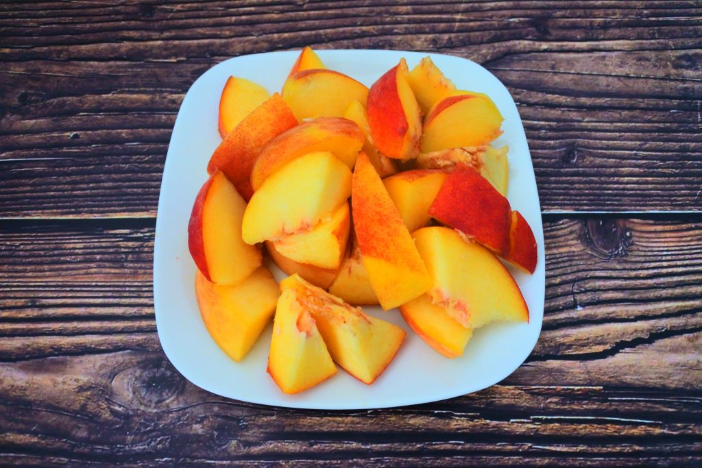 An angled image of a plate of fresh peach pieces