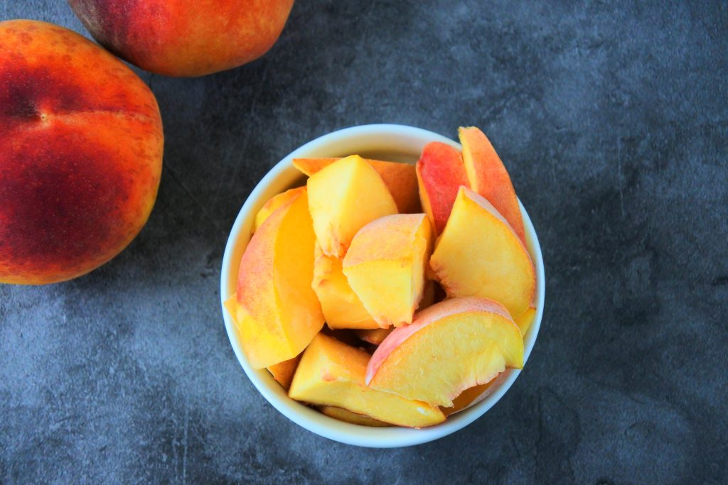 An overhead image of a bowl of frozen peach chunks with whole fresh peaches in the top left corner