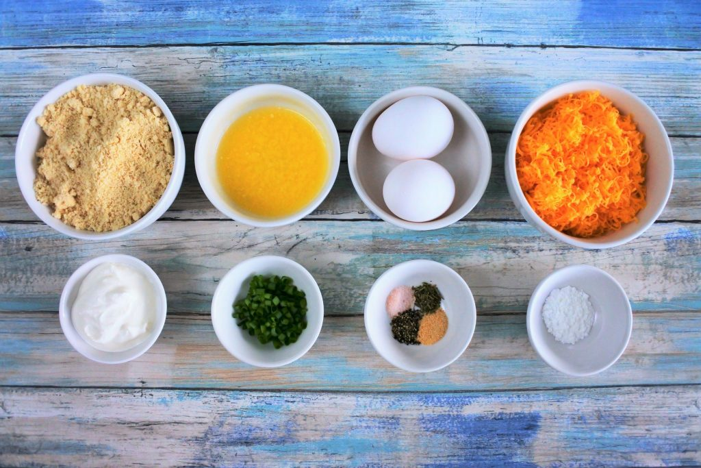 An overhead image of bowls of ingredients for An overhead image of bowls containing wet and dry ingredients for sour cream and chive cheddar biscuits including blanched almond flour, melted butter, eggs, finely shredded cheddar cheese, sour cream, chives, salt, pepper, Italian seasoning, garlic powder and baking powder