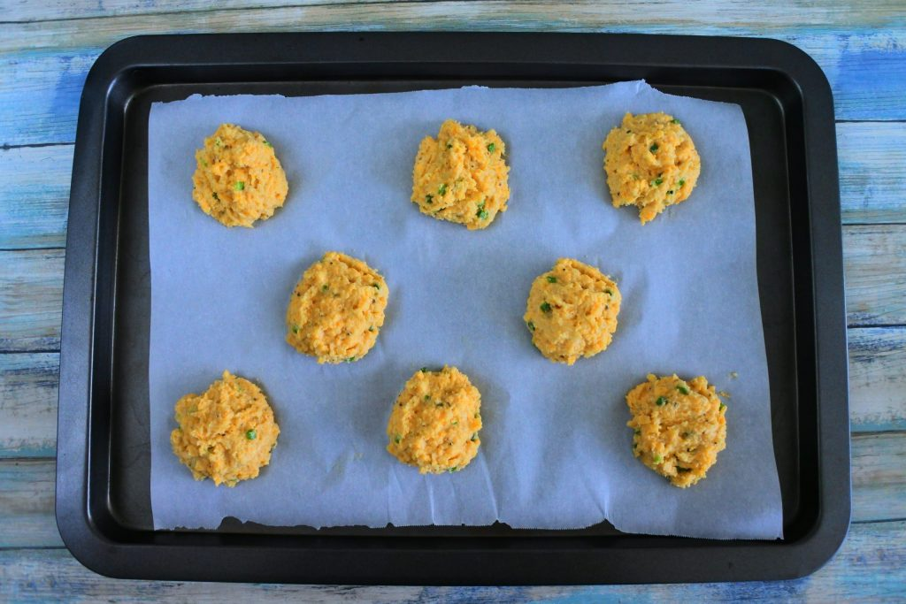 An overhead image of a parchment lined tray with unbaked sour cream and chive cheddar biscuits