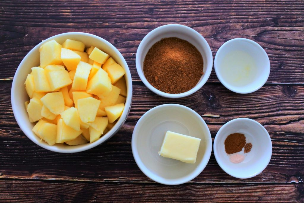 An overhead image of bowls of ingredients for Southern Fried Apples including fresh apple chunks, coconut sugar, lemon juice, butter and spices including salt, nutmeg and cinnamon