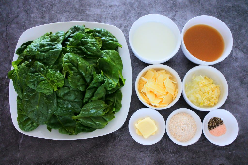 An overhead image of a plate of fresh spinach, and bowls containing milk, broth, Parmesan cheese, diced onions and garlic, butter, white whole wheat flour and salt and black pepper