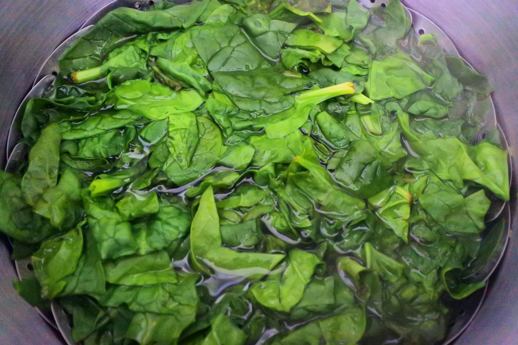 An overhead image of fresh spinach in a pot of water.