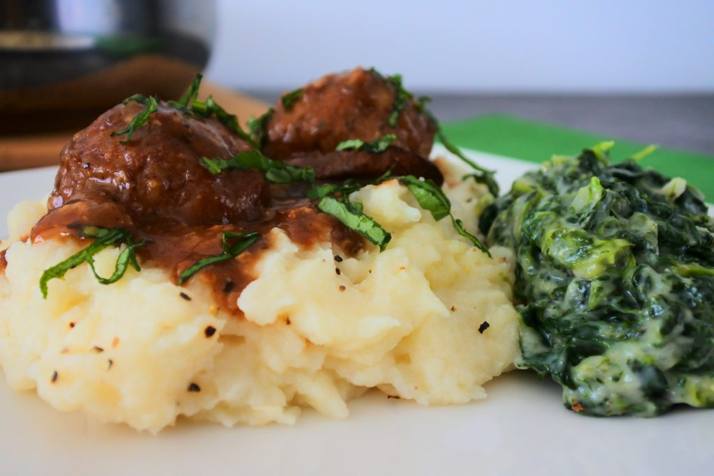 A close up image of mashed cauliflower topped with salisbury meatballs and served with a side of creamed spinach