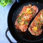 An overhead image of seared steak topped with garlic and thyme in a cast iron skillet with a cropping of herbs in the top left edge