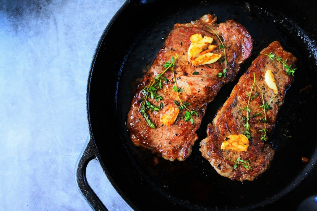 An overhead image of seared steak topped with garlic and thyme in a cast iron skillet
