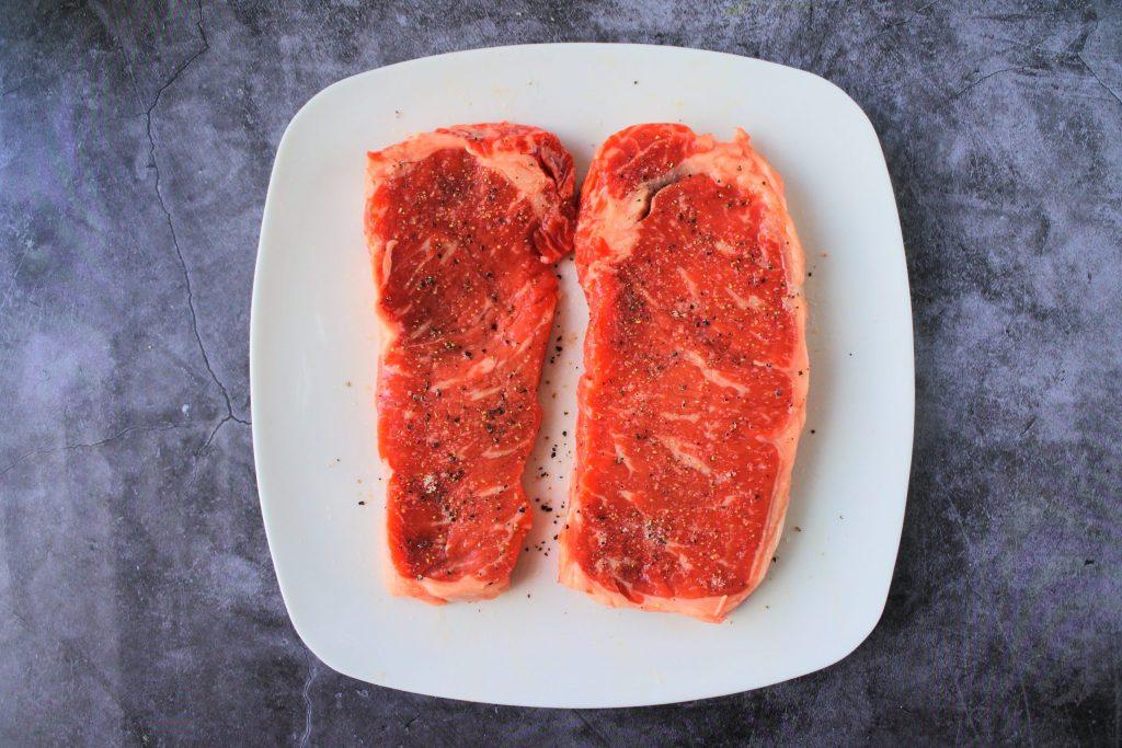 An overhead image of salt and pepper seasoned steaks on a plate