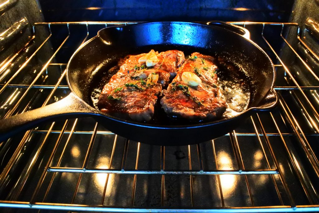 An image of seared steak in a cast iron skillet that's been placed in the oven