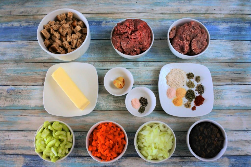An overhead image of plates and bowls of ingredients including croutons, ground beef, ground pork, a stick of butter, roasted garlic, spices, celery, carrots, onions, and raisins