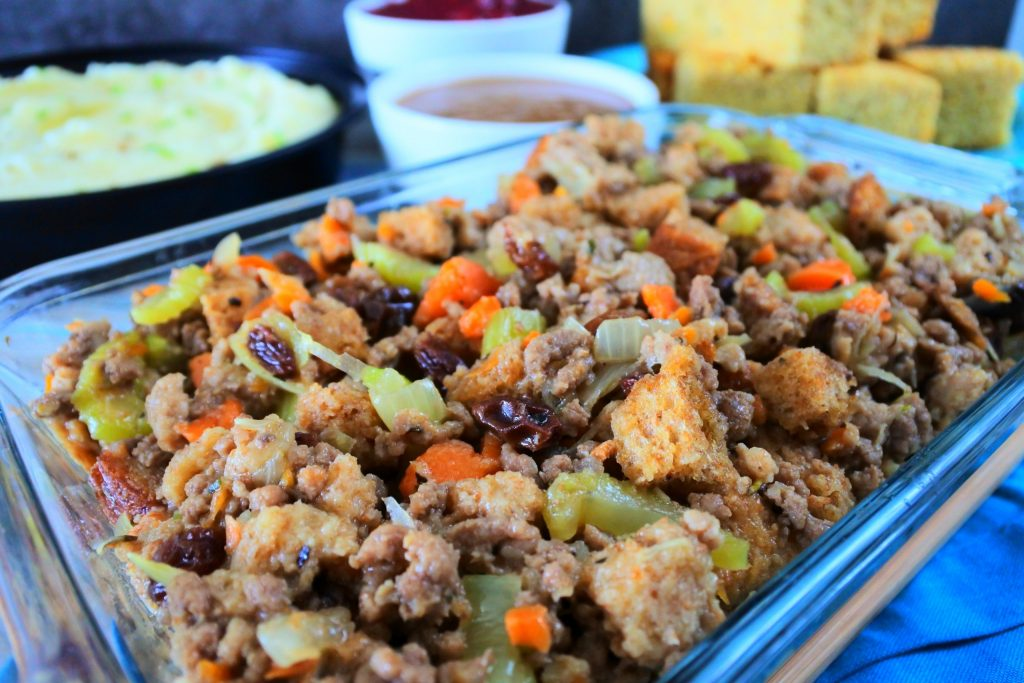 An angled image of a dish of stuffing/dressing with other sides in the background