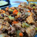An angled close up image of a dish of stuffing/dressing with other sides in the background