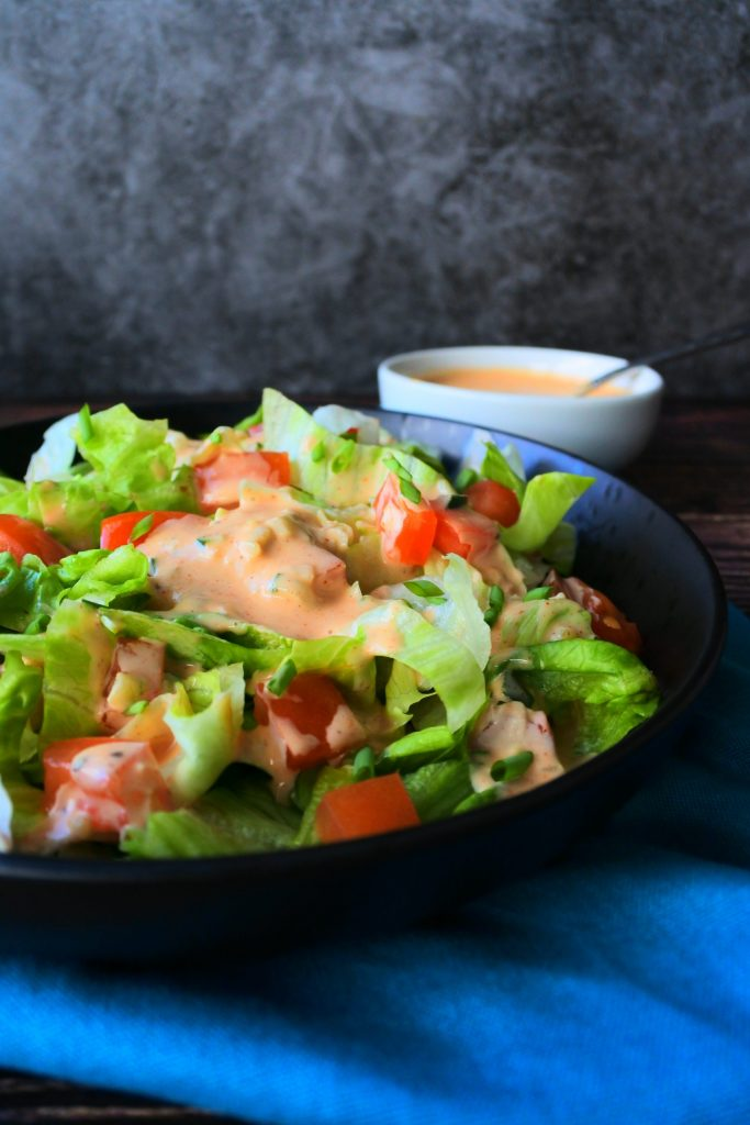 An angled image of a dish with a salad topped with homemade thousand island dressing on a blue napkin with a dish of thousand island dressing in the background