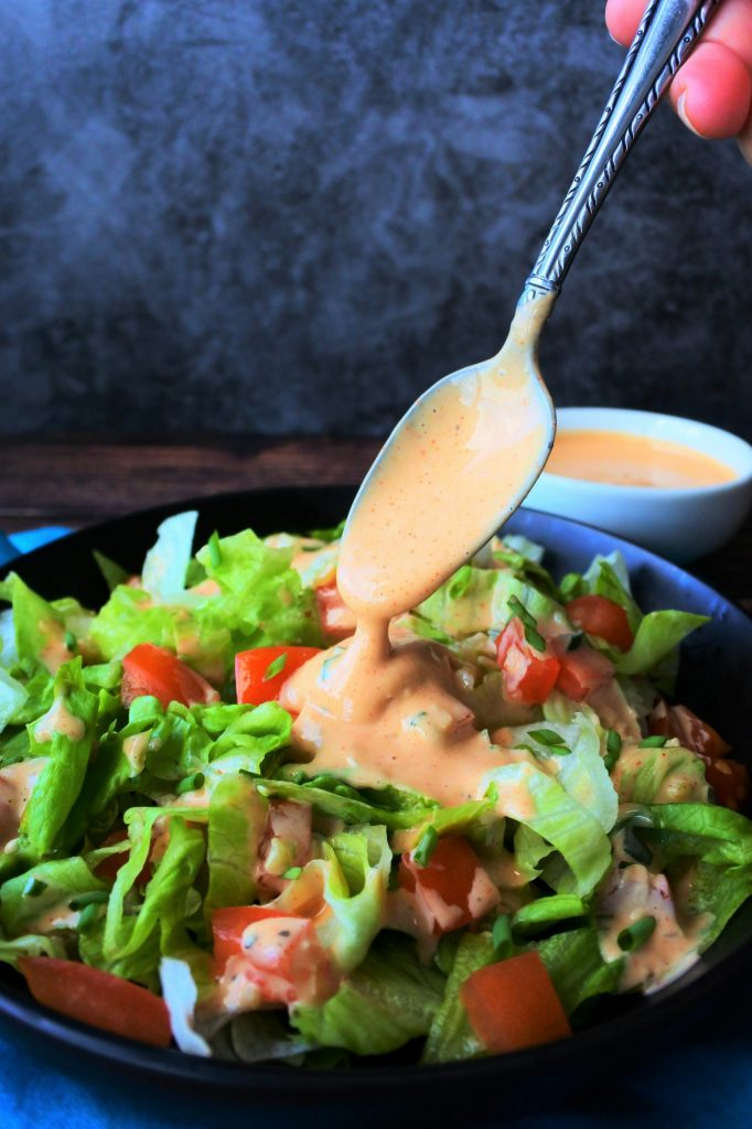An angled image of a dish with a salad being topped with homemade thousand island dressing on a blue napkin with a dish of thousand island dressing in the background