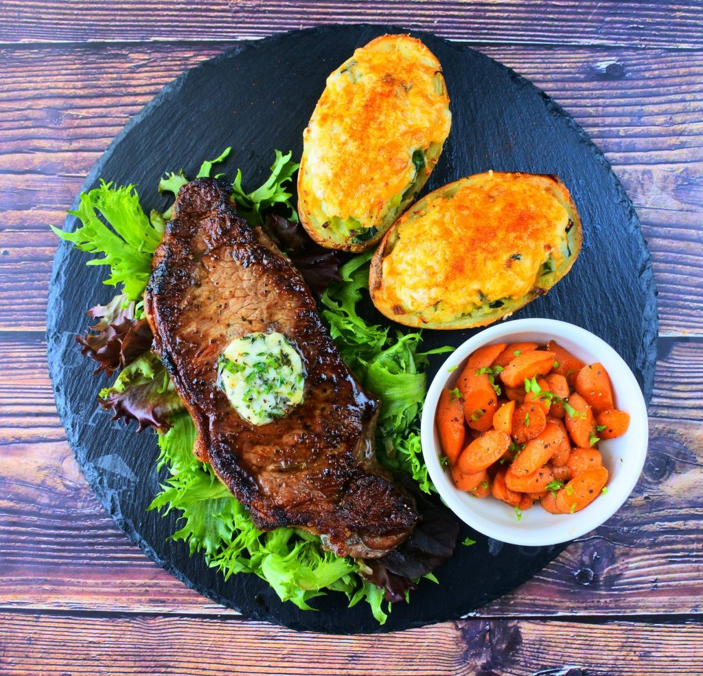 An overhead image of a slate plate with a seared steak on a bed of greens topped with a composite butter, a small dish of honey glazed carrots and two cheesy twice baked potatoes with leeks