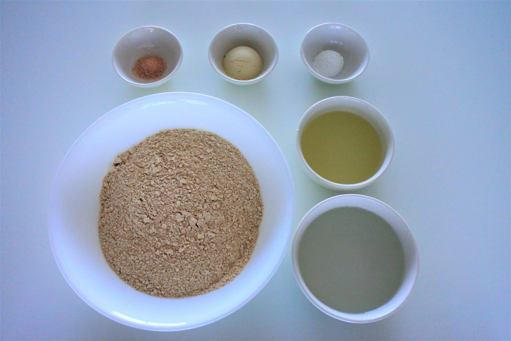 An overhead image of bowl containing the following ingredients: Himalayan salt, vital wheat gluten, baking powder, white whole wheat flour, oil and water